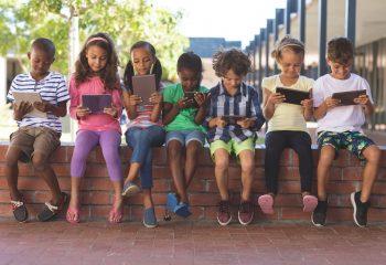 Students using digital tablet at corridor in school